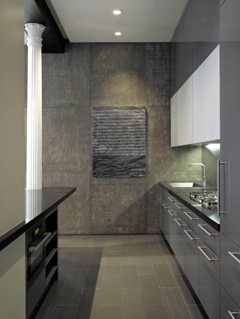 This small and narrow kitchen has a concrete gray flooring and wall that matches with the sleek gray cabinets and drawers of the kitchen island and peninsula with black countertops contrasted by the white pillar and ceiling.