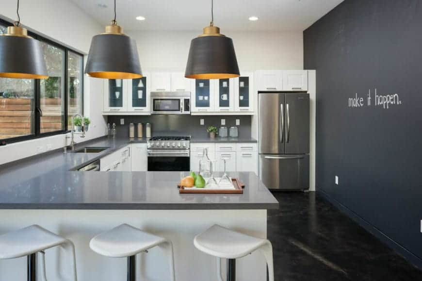 This industrial-style kitchen has a U-shaped peninsula with a gray countertop that complements the white kitchen cabinets and drawers and matches the stainless steel appliances. This is contrasted by a black wall with word artwork on it.