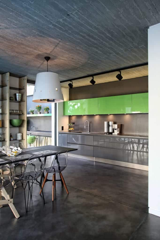 The concrete gray industrial-style flooring is a reflection of the ceiling that has a row of black spot lights mounted on it. This is matched with the dark gray walls and cabinets of the peninsula that makes the green floating cabinets stand out.