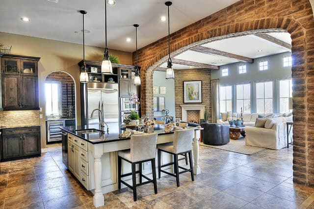 There is a large arched entryway going into this kitchen. This entryway is made of adobe bricks that matches the gray hue of the flooring tiles. This makes the white wooden kitchen island stand out with its black countertop.
