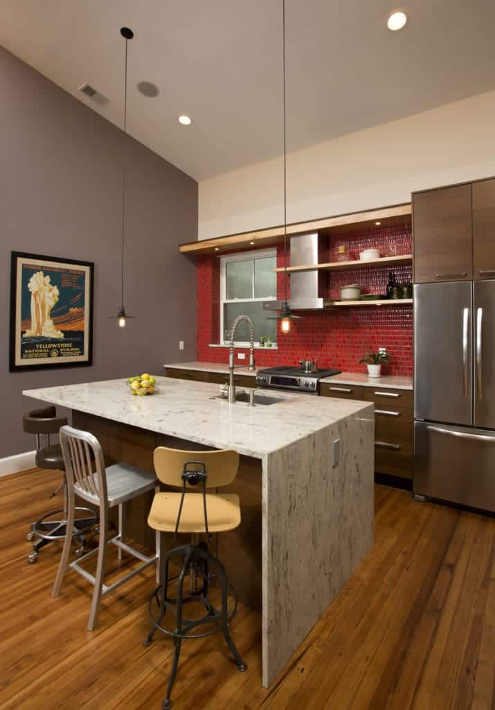 The simplicity of this kitchen is elevated to a higher level with its combination of different hues. It has a white shed ceiling, gray wall and hardwood flooring. The white marble waterfall kitchen island stands out against this as well as the red backsplash tiles.