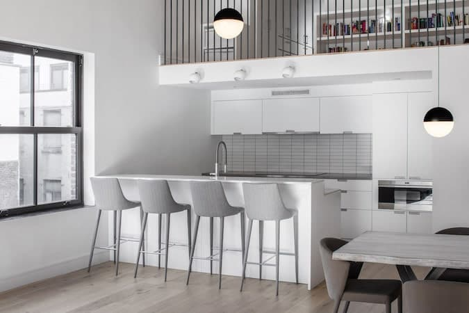 This industrial-style kitchen is right under the railings of the second level loft. The railings go well with the contrasting white walls that blend with the cabinets and drawers of the peninsula and kitchen island that is complemented by the gray countertop and backsplash.