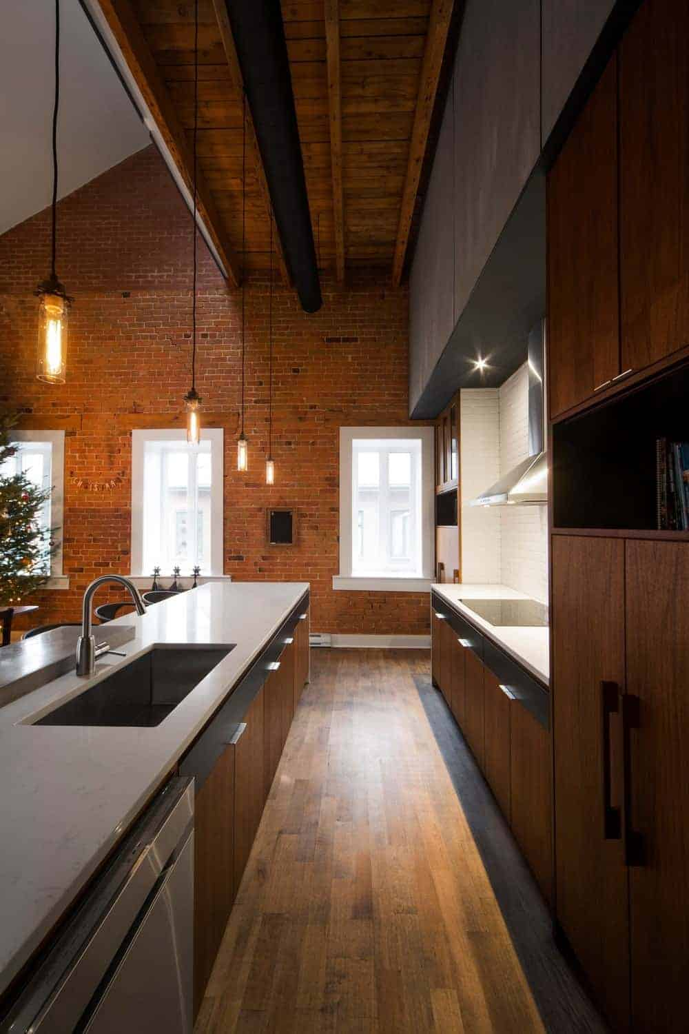 The narrow hardwood flooring of this Industrial-style kitchen matches with the brown wooden cabinetry of the flanking kitchen island and kitchen peninsula with white countertops and stainless steel appliances with a nice background of a brick wall with contrasting white windows.