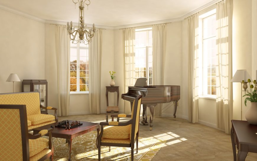 Small living room featuring a gorgeous chandelier and a piano on the side. The seats are lovely as well as the white window curtains.