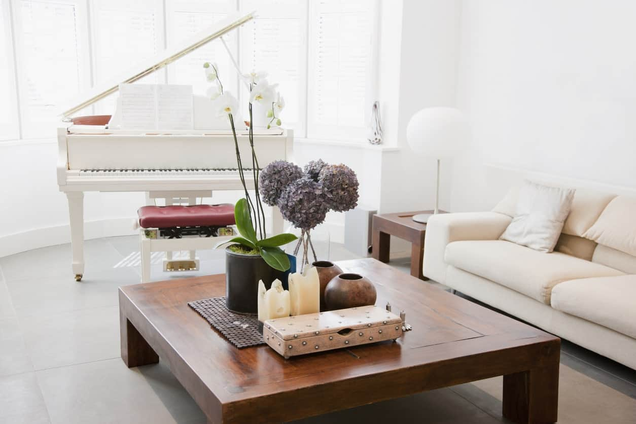 White living room featuring a cozy couch and a stylish center table along with the white piano matching the walls and ceiling.