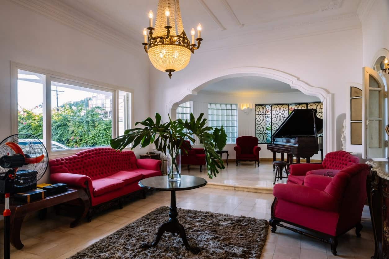 Large formal living room offering a very elegant set of red velvet seats. The space is lighted by a gorgeous ceiling light. It also offers a black piano.