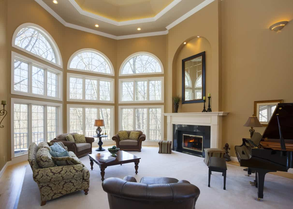 An elegant formal living room featuring a high ceiling and a massive rug covering the hardwood flooring. The room also offers a fireplace and a handsome piano.