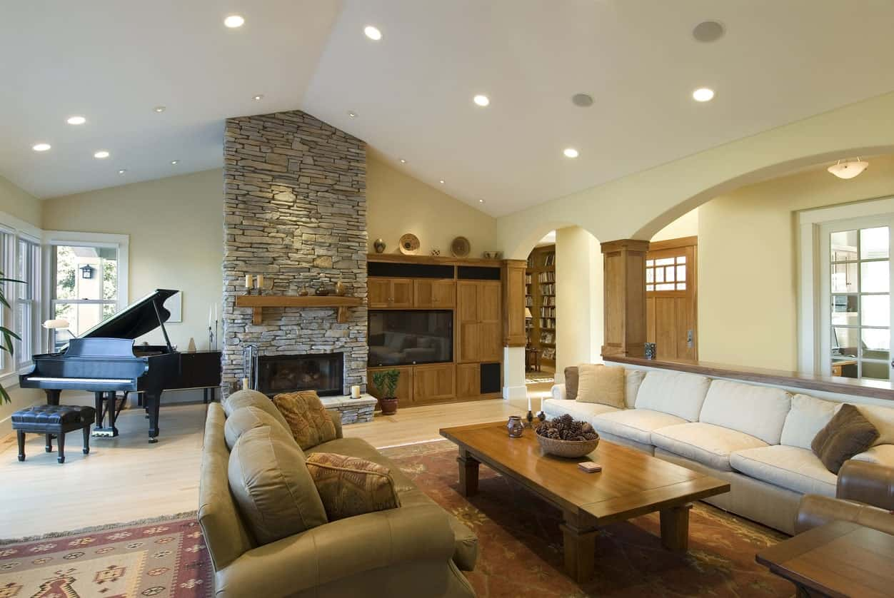 Large formal living room featuring a brick-style fireplace and a grand piano on the corner. There's a TV beside the fireplace as well.