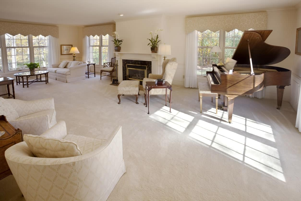 Spacious formal living room offering classy seats and a fireplace along with a grand piano set on the carpet flooring.