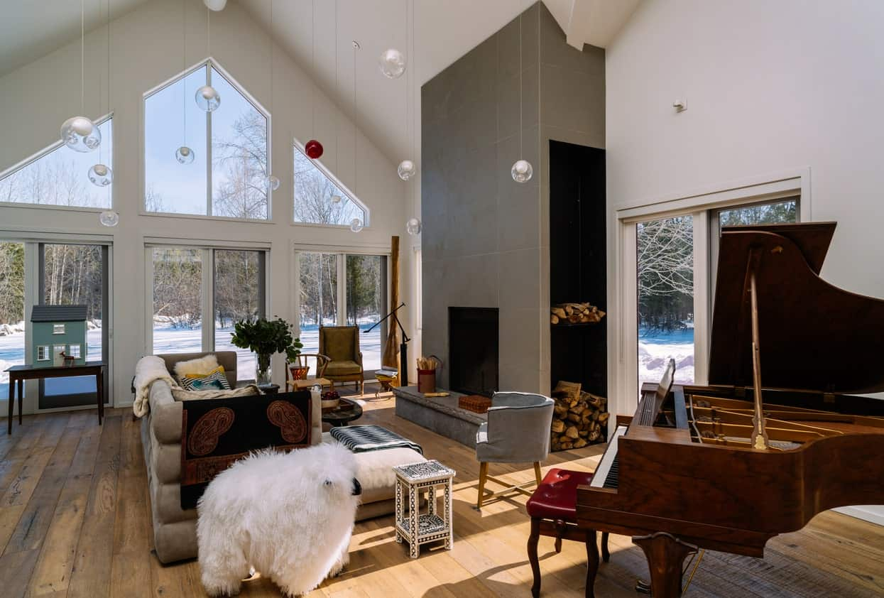 Large living space boasting a modish fireplace and a comfy set of seats along with a very charming piano on the side.