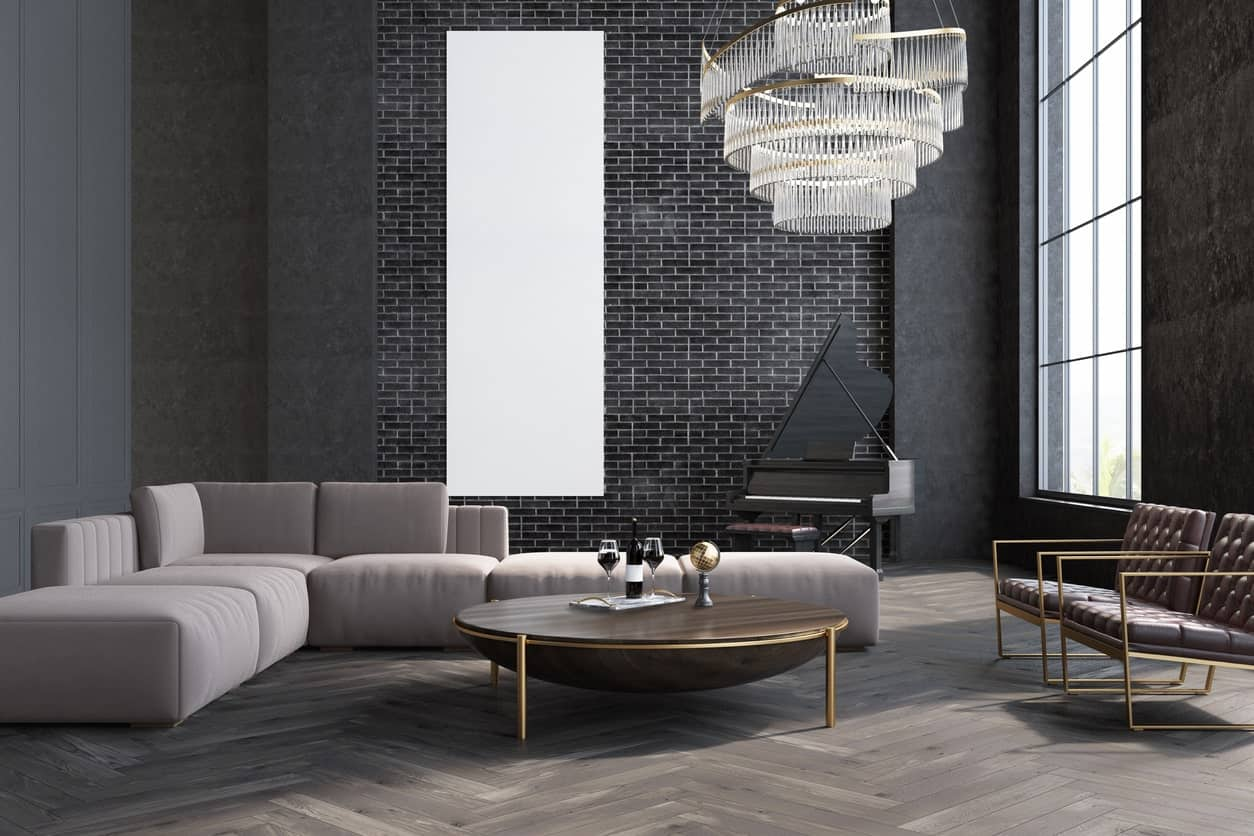 A stylish formal living room with black walls and a stunning ceiling lighting. The sofa set looks perfect together with the hardwood flooring.