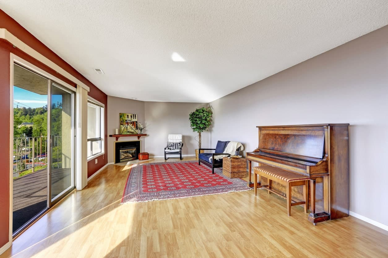 Spacious living space featuring a nice set of seats and a vintage piano adding class to the home.