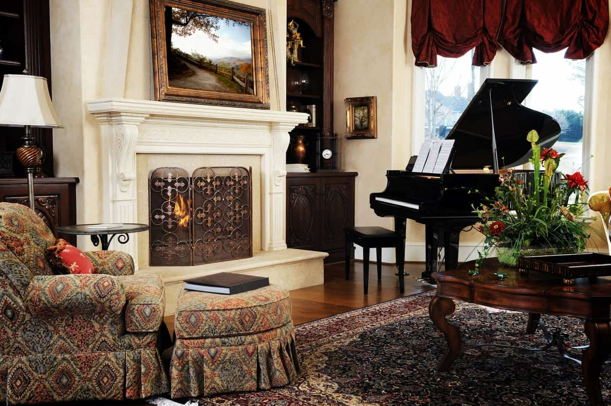 This formal living room is oozing with elegance with its seats and fireplace along with its rug and black piano that looks very handsome.