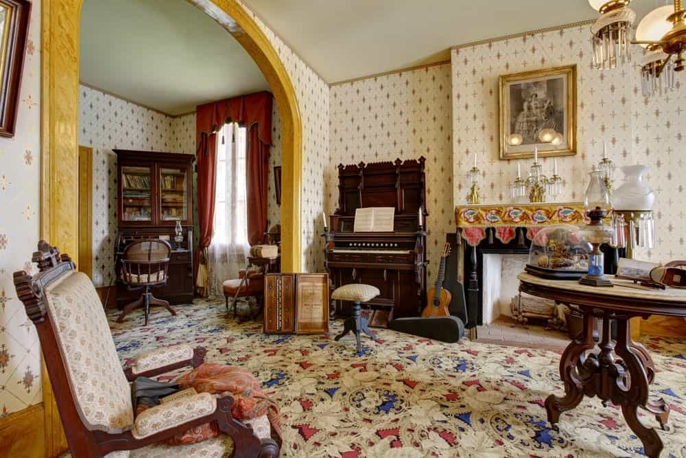A classy living room featuring charming walls and floors along with a vintage piano and classy seats.