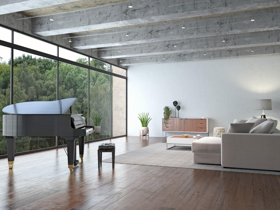 A large formal living room boasting a cozy sofa set in front of the floor-to-ceiling glass windows overlooking the magnificent outdoor views. There's a grand piano as well, set on the hardwood flooring.