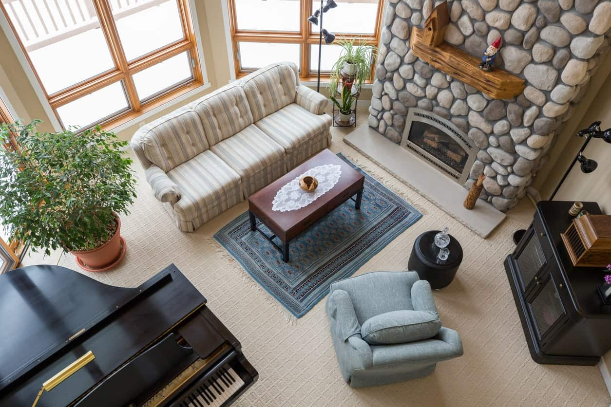A classy formal living room featuring a set of comfy seats and a grand piano set on the carpet flooring. The fireplace looks very attractive.