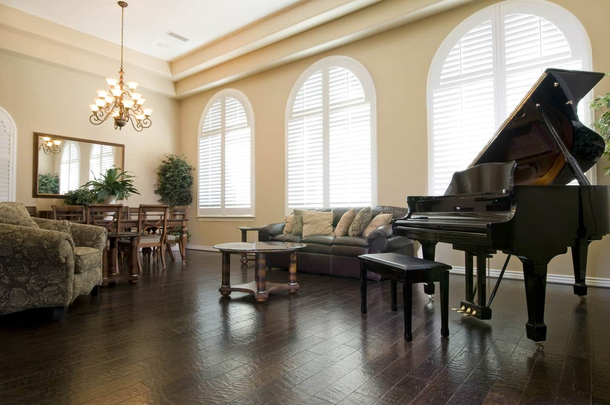 A classy living space featuring an elegant sofa set and a black piano set on the hardwood flooring and lighted by a gorgeous chandelier.