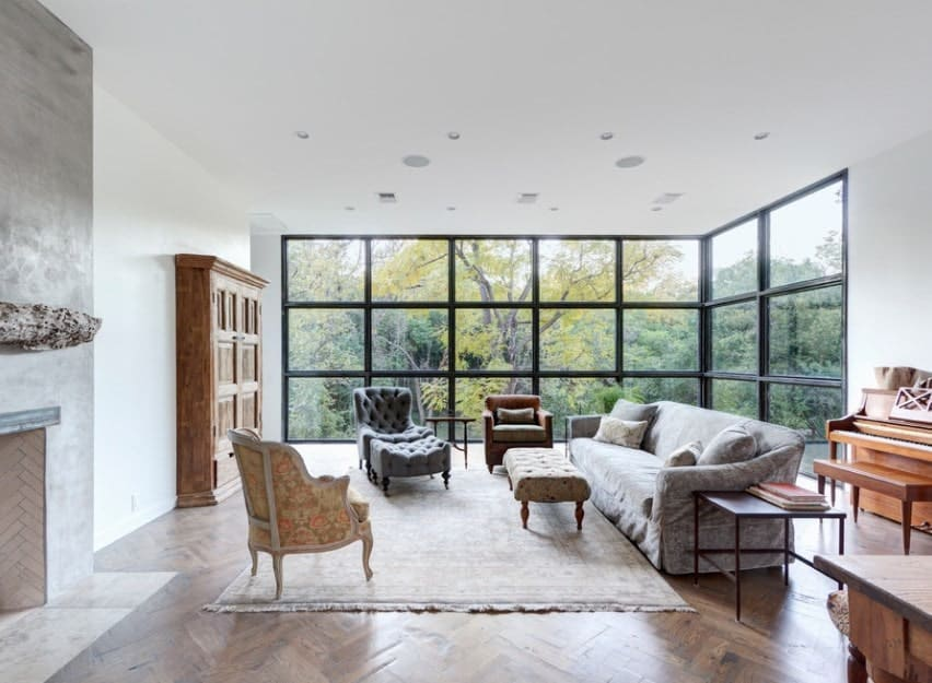 A spacious living room with an elegant set of seats and a stylish herringbone hardwood flooring along with floor-to-ceiling glass walls overlooking the beautiful outdoor views.