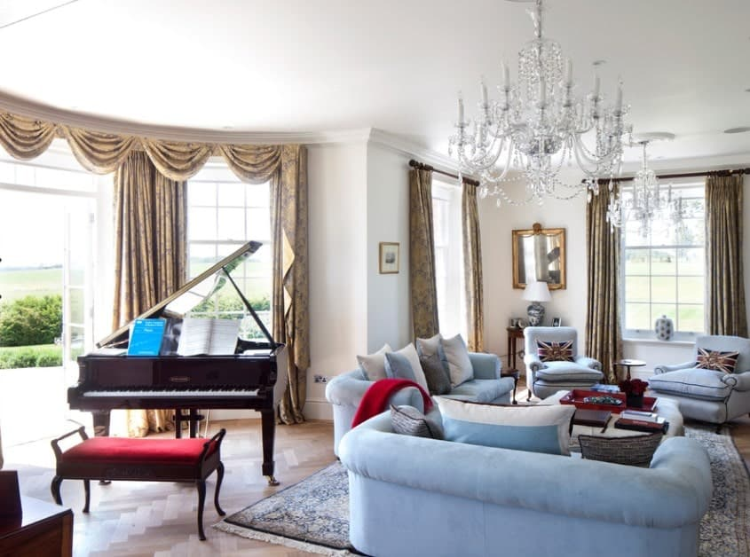 This formal living room offers cozy blue seats lighted by glamorous silver chandeliers. There are classy window curtains and a piano set on the herringbone hardwood floors.