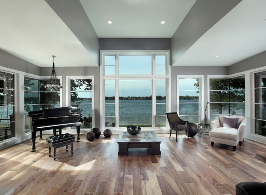 A spacious living room featuring hardwood floors and gray walls along with an elegant black piano on the corner.