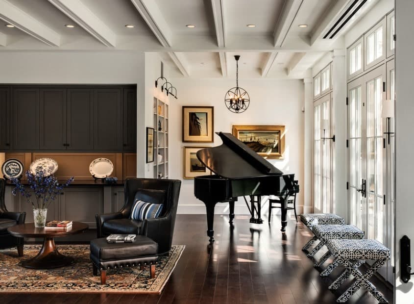 This living room offers stylish and classy seats along with a grand piano on the side, set on the hardwood flooring.