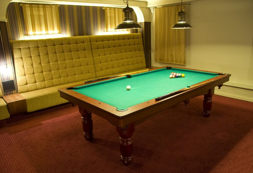 This man cave features a classy red carpet flooring along with the stunning seats and the billiards pool lighted by pendant lighting.