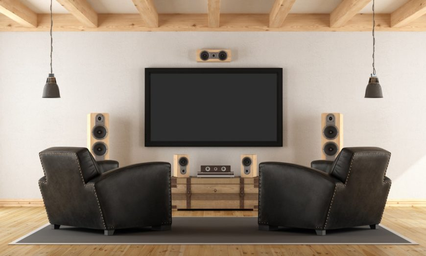 This man cave features a widescreen TV and a sound system along with elegant black seats lighted by classy pendant lights.