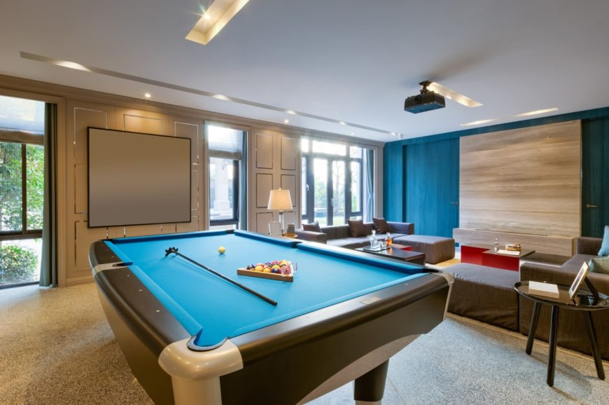 Large man cave featuring a cozy living space with a blue wall along with a billiards pool set on the carpet flooring under the stunning ceiling.