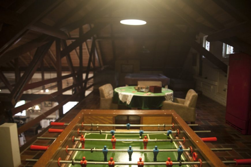 This man cave boasts multiple gambling table sets lighted by a classy pendant lighting.
