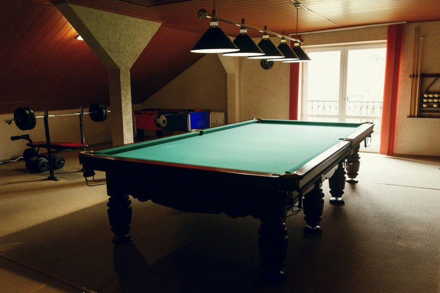 This man cave boasts an elegant billiards pool set on the carpet flooring and lighted by classy pendant lights.