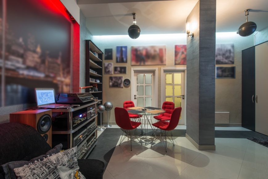 This man cave features a sound system along with a small round table set near the shelves. The lighting looks absolutely perfect with the room's style.