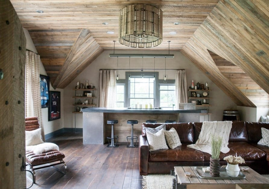 A rustic man cave featuring a stunning ceiling and hardwood flooring. The room features a bar area and a sofa set.