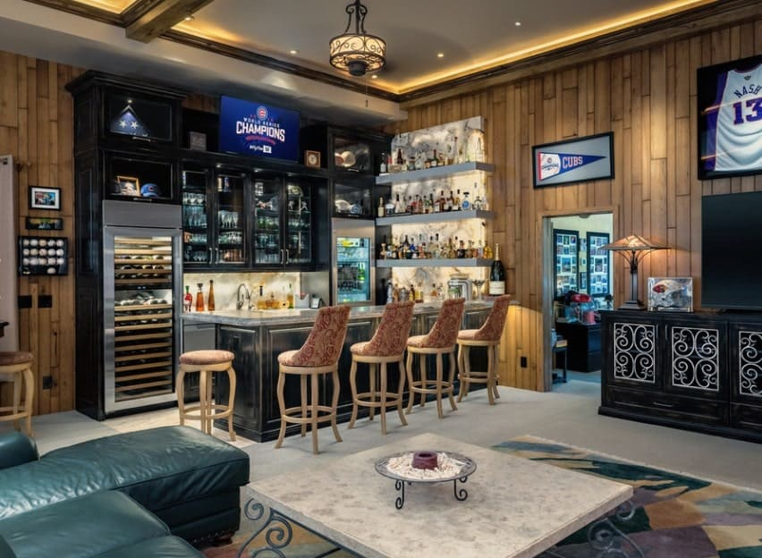 Large man cave featuring a classy bar area with lots of shelving and cabinetry along with a comfy sofa set on top of a stylish rug.
