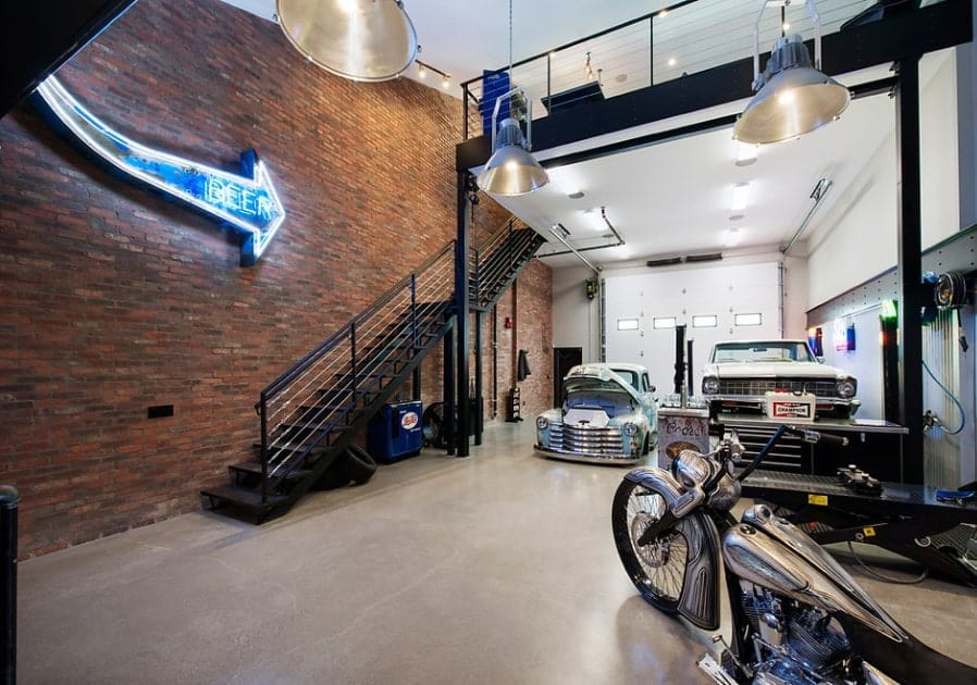 Large garage-type man cave featuring model cars and motorcycle. The tall brick wall looks so stylish.