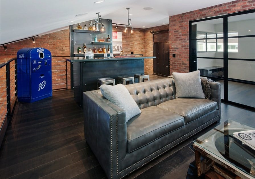 This man cave features brick walls and hardwood flooring. The room also features a cozy living space and a classy bar area.