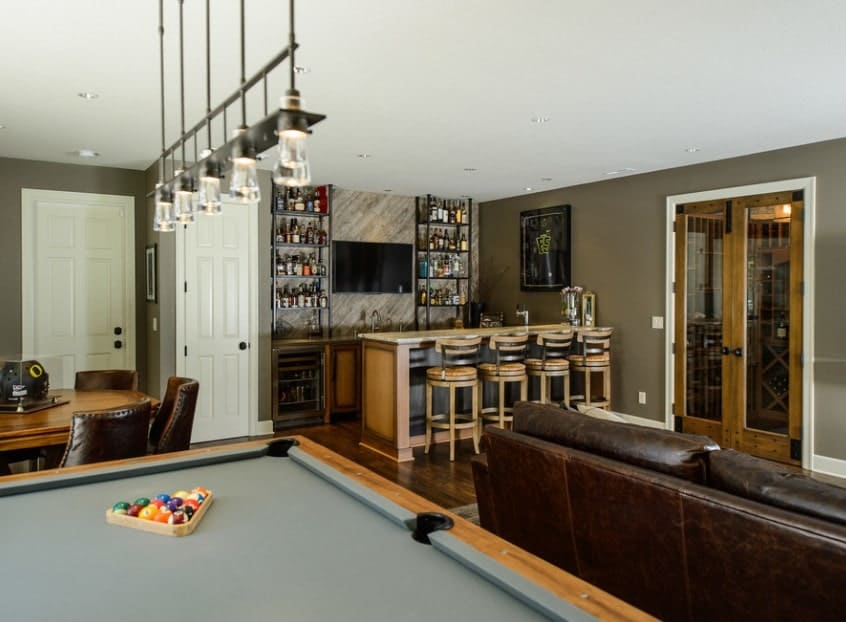 Large man cave featuring a classy bar area and a living space, along with a billiards pool lighted by pendant lighting.