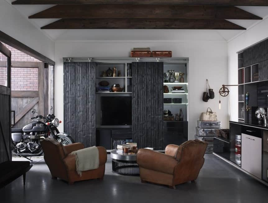 This man cave boasts a model motorcycle along with a comfy set of seats with a stylish center table. The TV stand and cabinetry feature a very stylish sliding door.