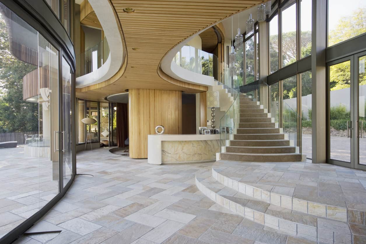 This is a spacious mansion foyer with light tones on its marble flooring tiles. These are further brightened by the natural lights coming in from tall glass windows that reach all the way to the high ceiling. This angle shows the wooden accent underneath the second floor catwalk.
