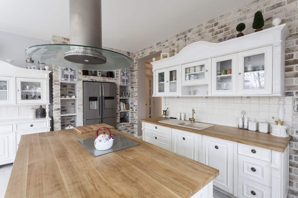 The brightness of this Mediterranean-style kitchen stems from its stark white cabinetry that is balanced by the brick walls lightly smeared with white paint. This is complemented by the butcher block countertops of the island and peninsula.