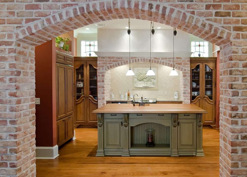 The brick arched entryway that leads to this Mediterranean-style kitchen mirrors the brick arched alcove of the cooking area creating a parallel that flanks the rest of the kitchen and its wooden cabinetry matching the hardwood flooring.