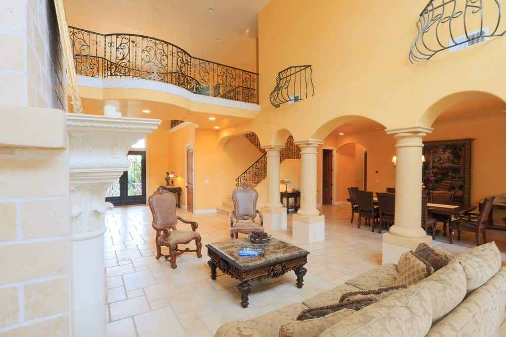 Large Mediterranean mansion with a cozy couch and center table set on the living room's tiles flooring.
