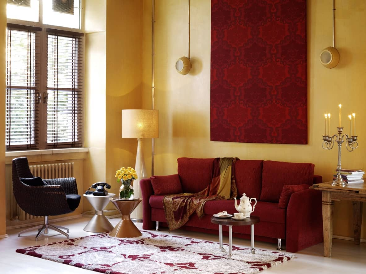 This Mediterranean living room offers a velvet red couch matching the wall decor behind it. The beige walls perfectly fits with the room's style and design.