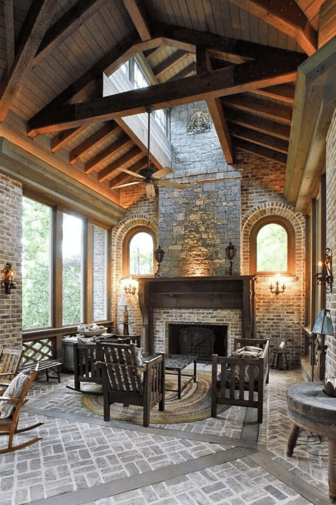 This Mediterranean-style living room showcases stone flooring, brick walls, and a towering vaulted ceiling with exposed beams. The room is furnished with dark wooden seats and a square coffee table over a round rug facing the fireplace.