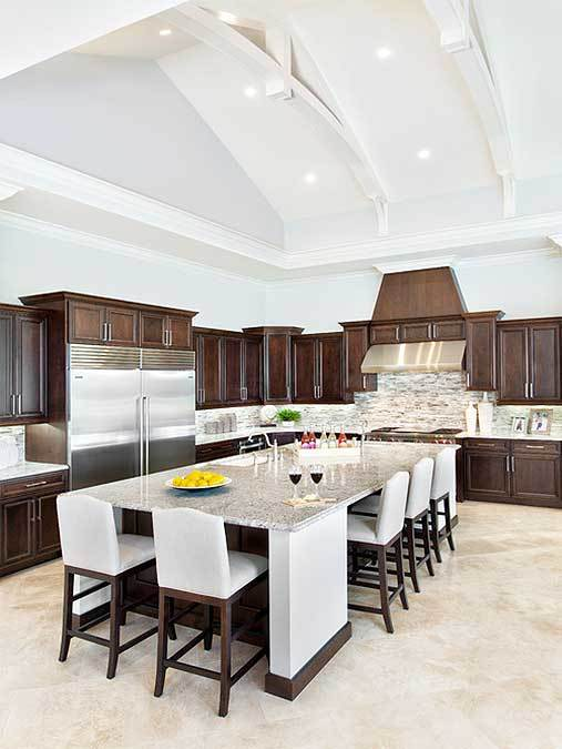 The cathedral ceiling of this Mediterranean-style kitchen has white exposed beams and recessed lights that brighten its hue matching with the white walls. These are contrasted by the dark brown L-shaped peninsula.