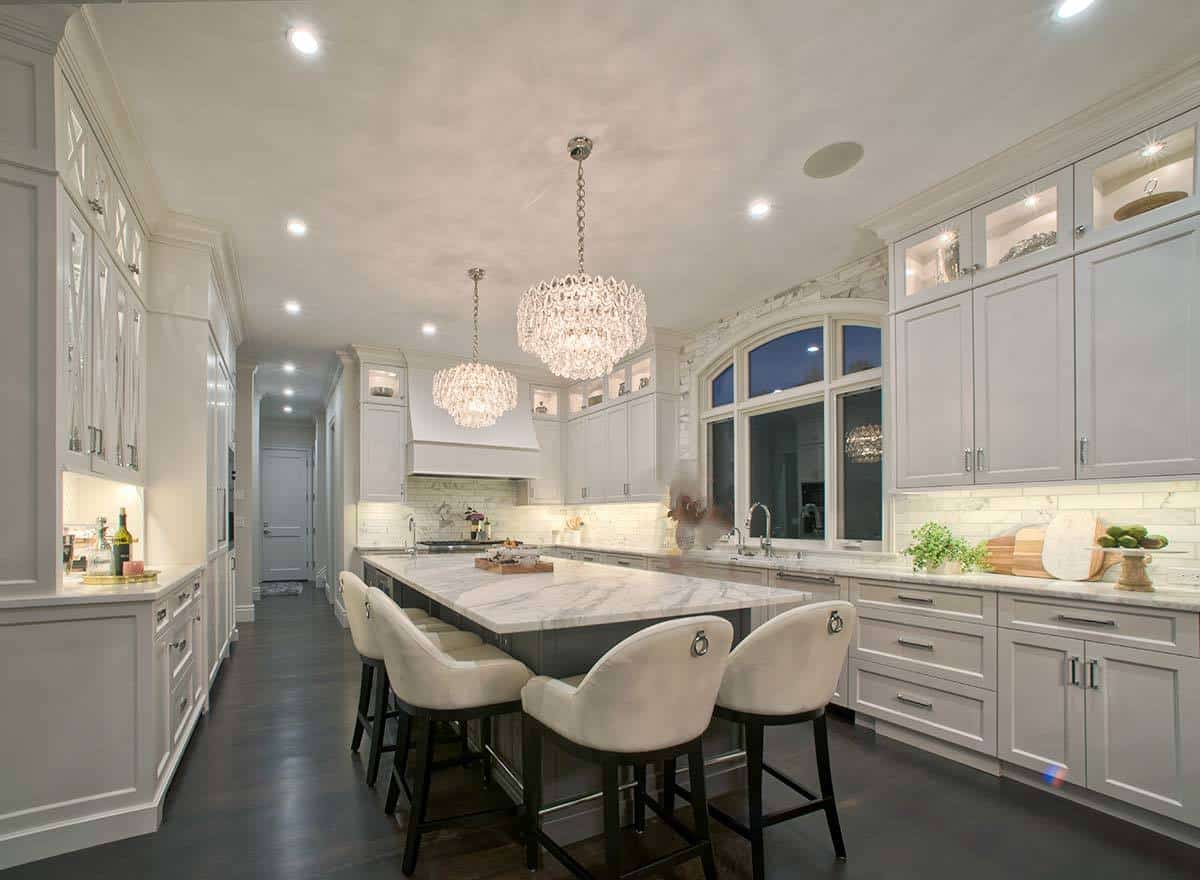The white arched window complements this predominantly white Mediterranean-style kitchen along with the two crystal pendant lights complementing the white marble countertop of the island and the peninsulas.