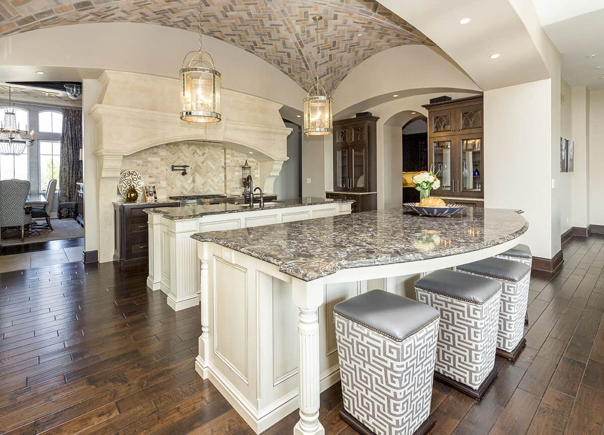 This Mediterranean-style kitchen has an impressive groin vault ceiling with herringbone pattern and two lantern pendant lights hanging over the two kitchen islands. This is paired with a large stone alcove for the cooking area with similar pattern on its backsplash.