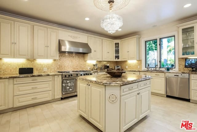 This is a predominantly beige Mediterranean-style kitchen that makes the stainless steel appliances stand out brightened by the brilliant crystal pendant light. This hangs over the small kitchen island with the same design as the L-shaped peninsula.