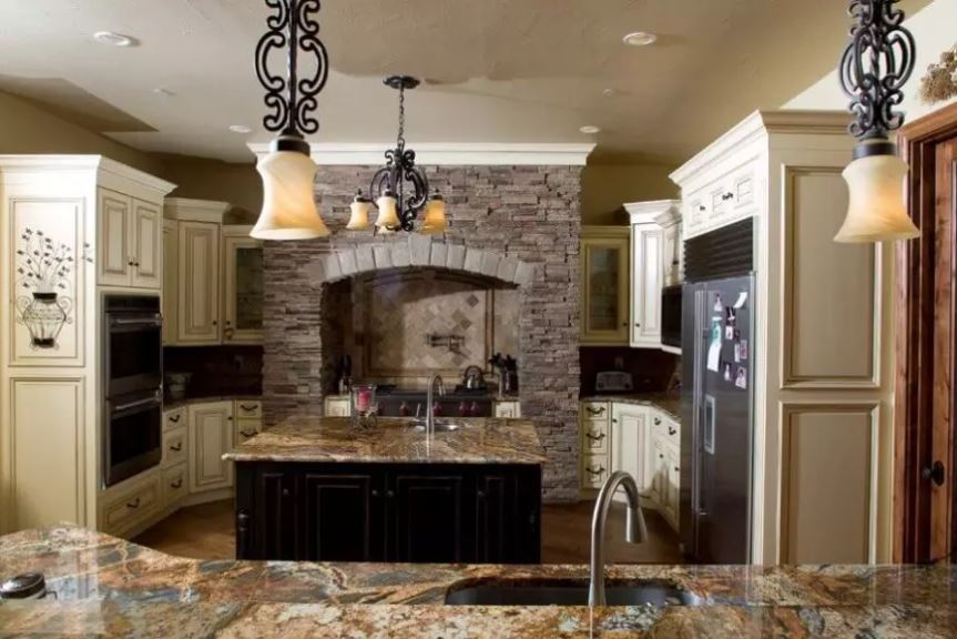 This charming Mediterranean-style kitchen has wrought iron pendant lights and a matching chandelier that complements the dark wood kitchen island and the textured stone alcove of the cooking area. This gives your kitchen a distinctive character.
