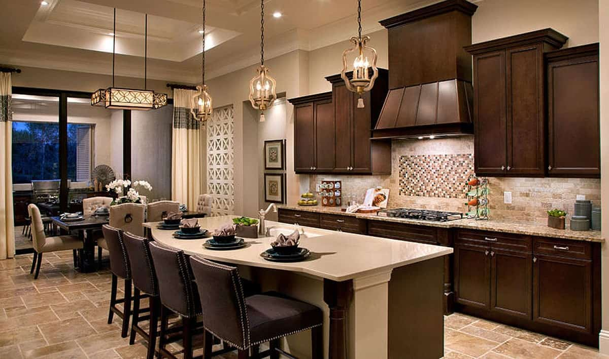 This is a beautiful Mediterranean-style kitchen with a bright beige coffered ceiling that hangs decorative pendant lights over the beige countertop of the kitchen island. These beige elements are contrasted by the dark brown hue of the cabinetry.