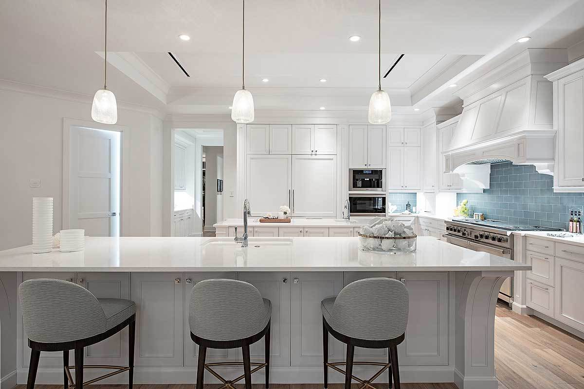 This is a bright and white kitchen with a white tray ceiling that blends with the elegant white cabinetry of the kitchen peninsula and kitchen island that are augmented by the recessed lights and pendant lights. These are then balanced by the gray tiles of the backsplash.